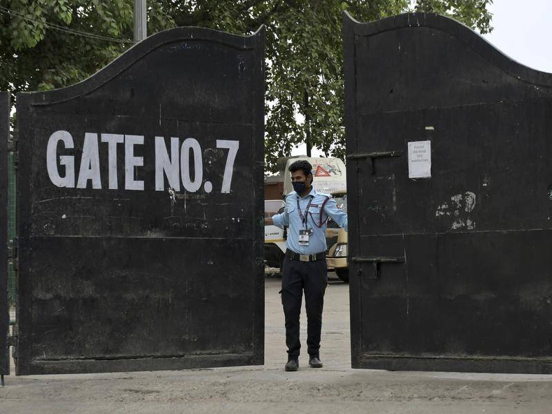 A guard closes a gate at an Indian Premier League venue after the tournament was suspended.