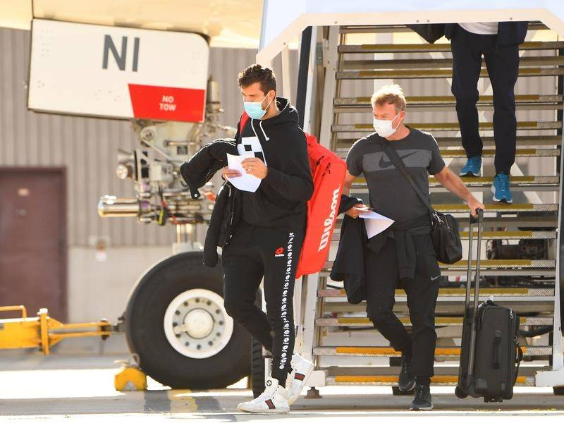 The first of 15 charter flights carrying tennis players and officials has touched down in Melbourne.